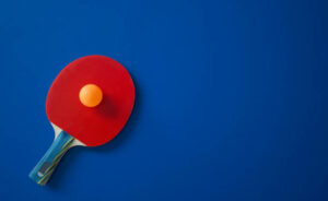 Red tennis racket lies on a blue table with a yellow ball